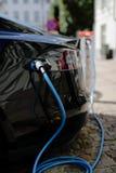 Électro voiture dans la recharge de ville Photographie stock