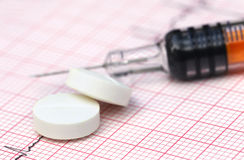Électrocardiographe avec les pilules et la seringue Photographie stock