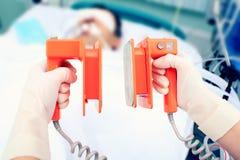 Électrodes de défibrillateur dans des mains Photos libres de droits