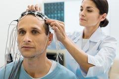 Électrodes femelles de fixation de docteur sur la tête du patient Image stock