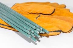Électrodes pour des gants de soudure pour des soudeuses sur un fond blanc Photographie stock libre de droits