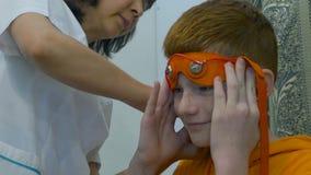 Électroencéphalographie européenne de conduite d'enfant Un fragment de processus Rheoencephalography - un docteur attache des éle Photos stock