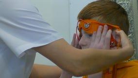 Électroencéphalographie européenne de conduite d'enfant Un fragment de processus Rheoencephalography - un docteur attache des éle Image stock