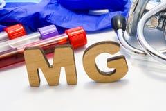 Électrolyte de magnésium de moyen d'abrégé de MG avec des tubes de laboratoire avec le sang et le stéthoscope Utilisant l'acronym photographie stock libre de droits