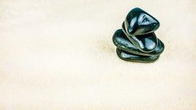 Élevage empilé de quatre cailloux noirs sur le sable blanc lumineux Image stock