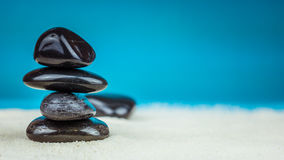 Élevage empilé de quatre cailloux noirs sur le sable lumineux avec le fond bleu Image stock