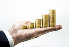 Élevage empilé par pièce de monnaie d'argent sur la main d'homme d'affaires Photographie stock libre de droits