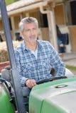 Éleveur de bétail conduisant le tracteur de jardin Photo stock