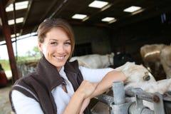 Éleveur de sourire de femme dans la grange Images stock