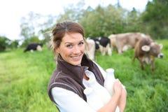 Éleveur heureux tenant le lait frais, vaches dans le dos Images stock