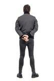 Élevez la vue arrière de l'homme dans les jeans serrés et la veste grise regardant loin Photo stock