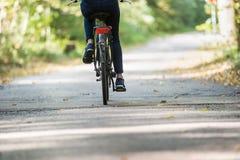 Élevez la vue cultivée d'une femme montant une bicyclette Images stock