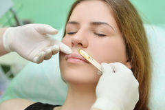 Élimination de la moustache d'une femme avec de la cire chaude dans un salon de beauté Image libre de droits
