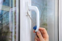 Élimination de la poignée d'une fenêtre en plastique utilisant le tournevis de main Photos stock