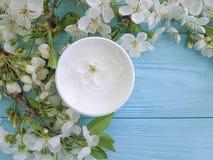 Élixir cosmétique crème nourrissant la cerise de floraison saine de traitement organique sur un fond en bois bleu Photos libres de droits