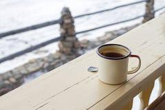 Émaillez la tasse avec le thé fort et le sachet à thé sur une barrière en bois sur un fond neigeux d'hiver Photographie stock libre de droits