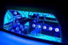 Émetteur à rayonnement ultraviolet pour les clous de séchage À l'intérieur de la Mener-lampe fonctionnante Image stock