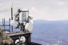 Émetteurs et antennes de télécommunication avec le fond de ville Images stock