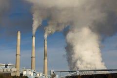 Émissions se levant des cheminées d'évacuation des fumées d'une usine de puissance de feu de charbon images libres de droits
