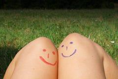 Émoticônes heureuses rouges et bleues peintes sur la peau Photographie stock libre de droits