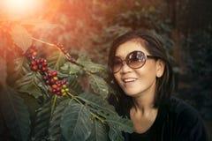 Émotion de sourire de bonheur de visage de femme asiatique près de graine crue de café sur la branche d'arbre images stock
