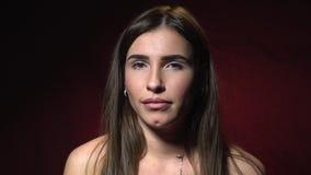 Émotions, confusion Une femme de brune avec des boucles d'oreille dans des ses oreilles prouve qu'elle ne sait pas quoi faire banque de vidéos