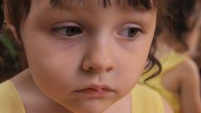 Émotions de l'enfant Une petite fille avec de grands yeux pleure Un enfant dans une robe jaune par le miroir banque de vidéos