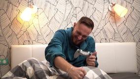 Émotions gagnant en jeu vidéo de type barbu dans la chambre à coucher dans le peignoir vert Émotions lumineuses dans le mouvement banque de vidéos
