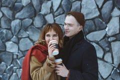 Émotions heureuses des couples dans l'amour passant le temps ensemble et buvant du café dehors pendant l'hiver Mur en pierre urba Photo libre de droits