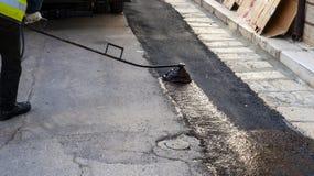 Émulsion de pulvérisation de bitume de travailleur de route Photographie stock libre de droits
