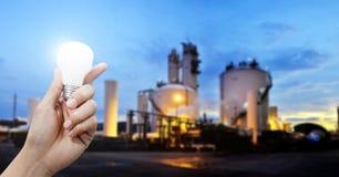 Énergie de la lumière pour l'industrie, main tenant l'ampoule dans le sujet industriel photo stock