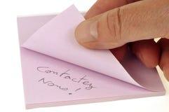 Éntrenos en contacto con escritos en un trozo de papel fotografía de archivo