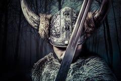 Épée, guerrier de Viking avec le casque au-dessus du fond de forêt Images stock