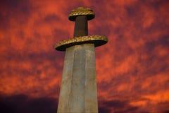 Épée médiévale de Viking contre un ciel dramatique Photographie stock