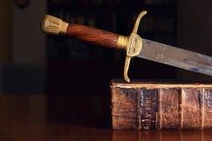 Épée sur la vieille bible image stock