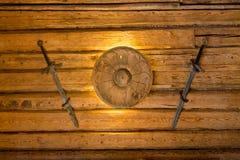 Épées de Viking et petit bouclier accrochant sur le mur en bois Photo stock