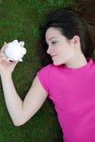 Épargnant regardant le piggybank Photographie stock