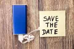 Épargnez le papier collant de note de date chargeant de la banque d'énergie Profondeur de champ sur la banque de puissance Photos libres de droits