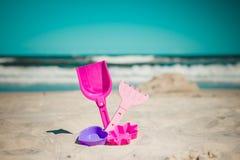 Épaule et jouets dans le sable sur la plage Images stock