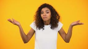 Épaules de gesticulation femelles afro-américaines, incertaines du choix, fond jaune banque de vidéos