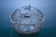 Épave de bateau dans le brouillard et l'eau calme Photographie stock libre de droits