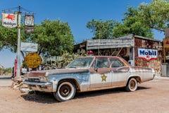 Épave rouillée d'un vieux de la voiture shérif à l'épicerie générale de Hackberry Image libre de droits