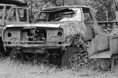 Épave rouillée de voiture dans la forêt en noir et blanc Photos libres de droits