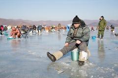 Éperlan de crochet de pêcheurs en hiver, Russie Photos libres de droits
