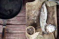 Éperlan de poisson frais avec des épices sur le panneau de cuisine Photos libres de droits