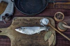 Éperlan gelé de poissons sur une planche à découper de cuisine Photos libres de droits