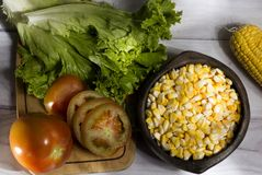 Épi de maïs et noyaux de maïs jaunes dans le vase à argile sur en bois blanc fond-accompagné par un zea riche mai de salade images libres de droits