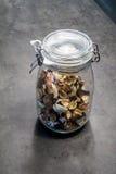 Épice et matière végétale sèches dans le pot en verre avec le couvercle fermé pour images libres de droits