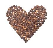 Épice la forme de coeur de poivre noir sur le blanc Images libres de droits
