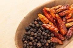 Épices chaudes : grain de poivre noir et poivrons de piment secs Images libres de droits